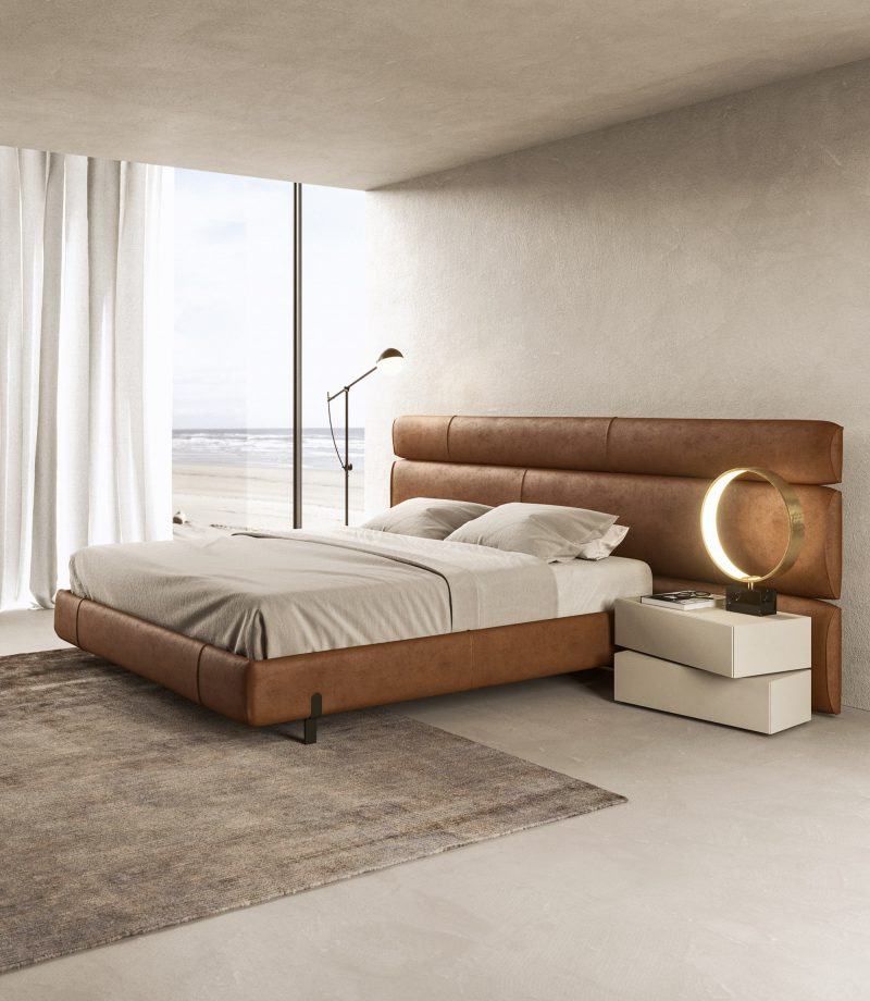 Niobe Niobe double bed characterized by the asymmetrical headboard. The model is upholstered with Danzica color 17 fabric and is equipped with feet in Brass metallic lacquer.