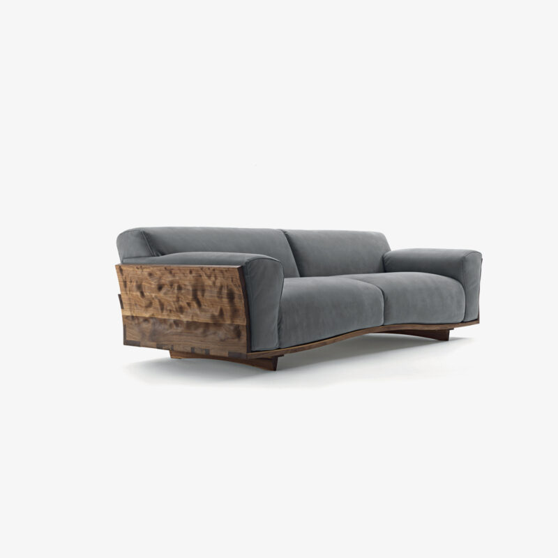Nudo Sofa with structure carved out of solid wood, with back and sides joined to each other through extraordinary dovetail joints which make the wood protrude outwardly, creating a sinuous and continuous motion.