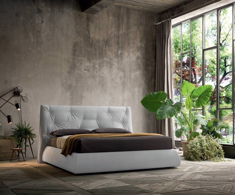 """LENNY The headboard's base widens and """"contains"""" the bed. Also the bed frame widens downwards but with a soft and evident curve, that anchors it to the floor."""
